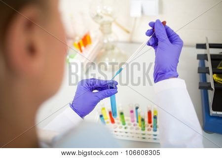 Close up view of lab technician sampling colorful liquids with glass pipette