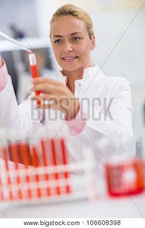 Attractive female chemical technician full test tubes with fluid using glass pipette