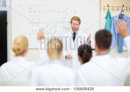 Male chemistry professor learning students in classroom
