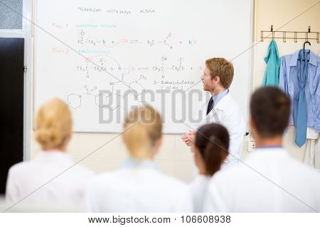 Young male chemical teacher teaching students in the classroom