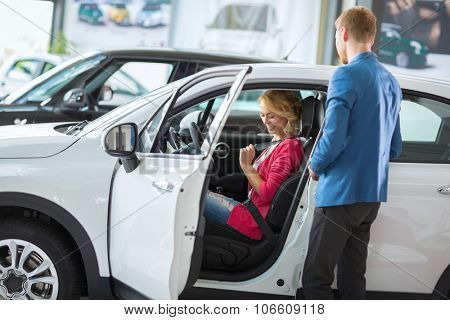 young woman test new model in the  car dealership saloon