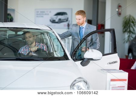 male customer in car showroom with car seller, young man sitting in car and  trying on the comfort of the car