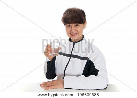 Good looking mature woman with glass of water posing after her sport session