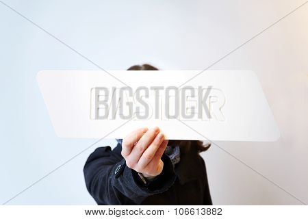 Woman holding a white sign saying faster. Shallow depth of field with focus on the sign and hand