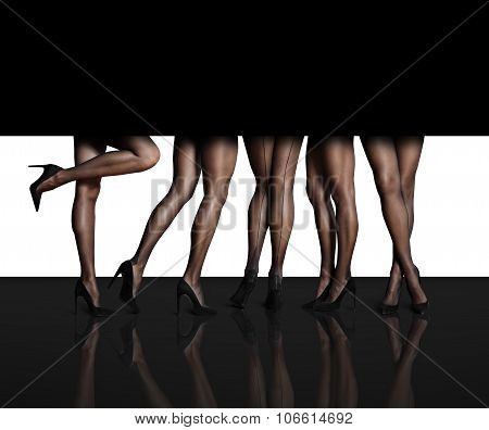 Women's Legs In  Different Position In A Black Space