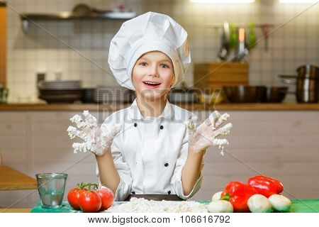 Funny happy chef boy cooking at restaurant kitchen and shows hands in the dough