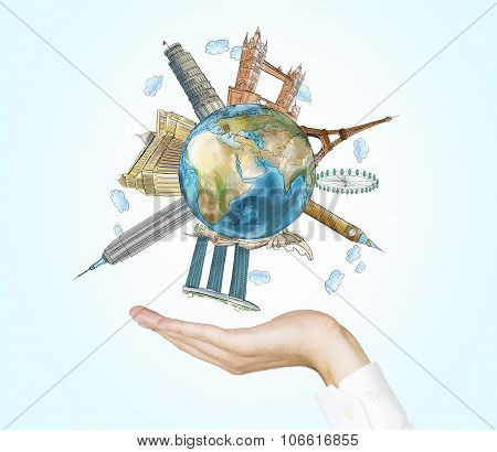 A Hand Holds A Globe With Sketched The Most Famous Places In The World. A Concept Of Tourism And Sig
