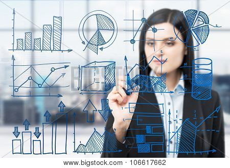 A Brunette Woman Is Drawing Some Business Charts On The Glass Screen. Modern Panoramic Office With N