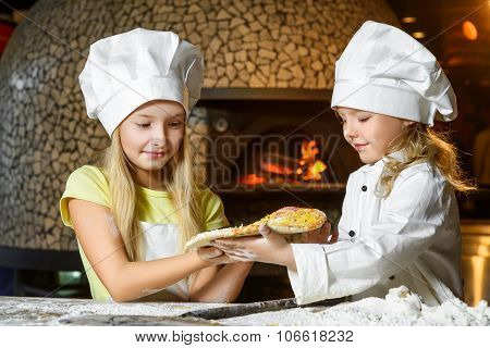 Funny happy chef girl cooking at restaurant kitchen and show pizza