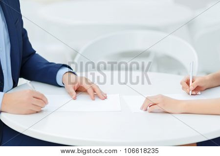 Two colleagues making personal notes.