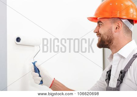 Attractive male worker is making house beautiful