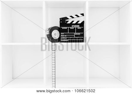 Movie Clapper Board And Film Reel On White Bookshelf