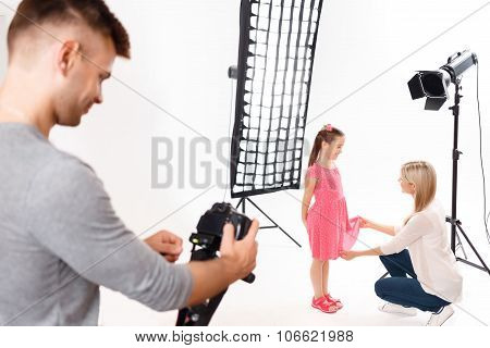 Photographer checks his camera while model is being prepared