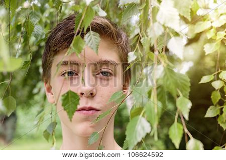 Portrait Of A Teenage Boy Hidden By Some Leaves