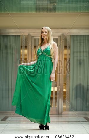 Portrait in full growth, young beautiful woman in a long green dress on the background showcases fashion boutique