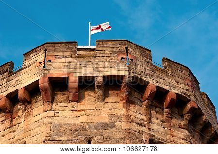 English flag on a pole top of medieval castle tower