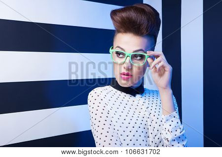 Attractive young woman wearing formal shirt and glasses on stripy background, beauty and fashion concept