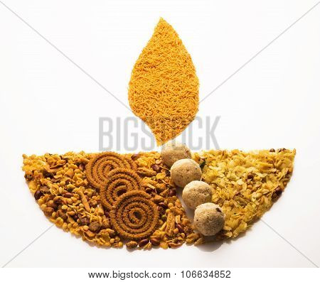 Traditional indian diwali snack or diwali food in diwali lamp form isolated on white. diwali greetin