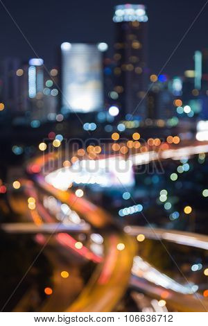 Abstract blurred bokeh lights highway intersection with city downtown at night