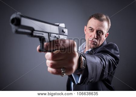 man in business suit with a gun