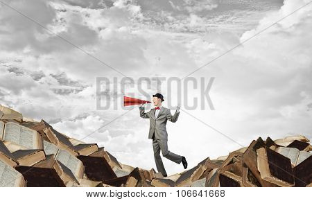 Young businessman on pile of books screaming emotionally in paper trumpet
