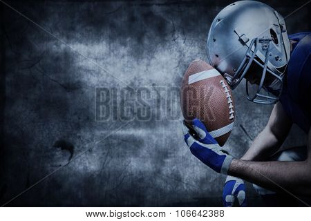 Close-up of upset American football player with ball against dark background