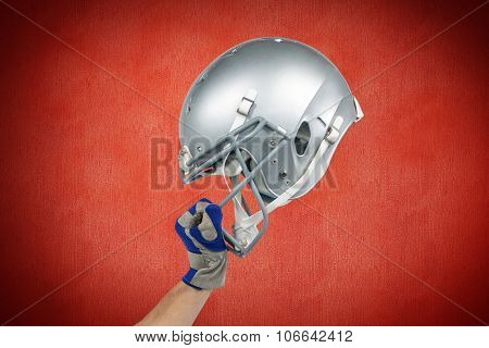 American football player handing his helmet against red background