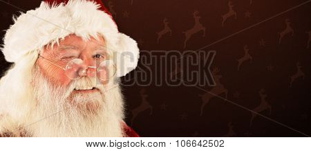 Santa claus winking against maroon reindeer pattern