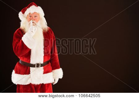 Santa asking for quiet to camera against dark brown background