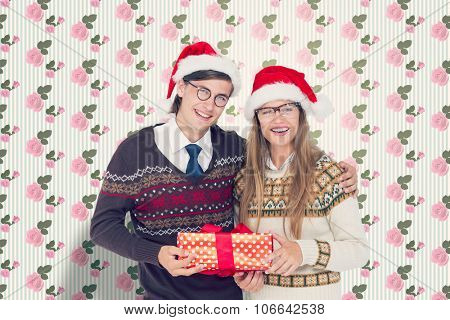Geeky hipster couple holding present against kitsch floral pattern wallpaper with roses