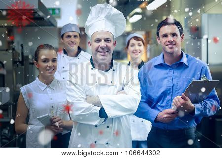 Snow against head chef posing with the team behind him