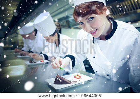 Snow against smiling chef garnishing dessert plate