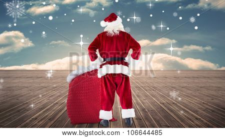 Santa with sack of gifts against wooden planks leading to blue sky