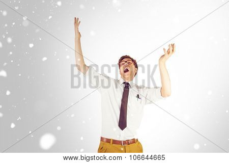 Geeky businessman standing with arms raised against snow