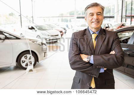 Smiling businessman with arms crossed at new car showroom