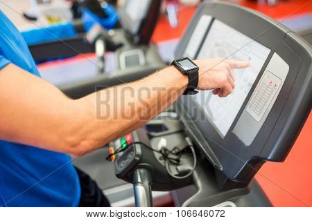 Man adjusting the settings of a treadmill at the gym