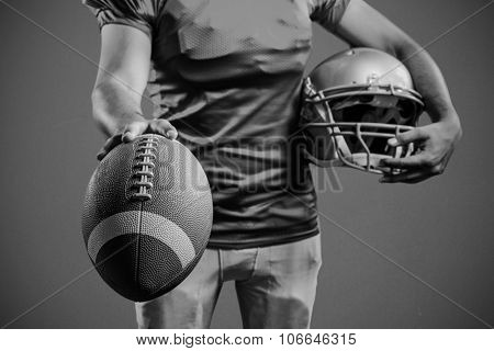 Mid section of sportsman showing American football while holding helmet against blue background