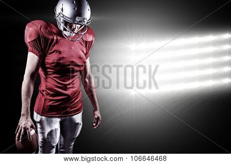 American football player looking down while standing against spotlight