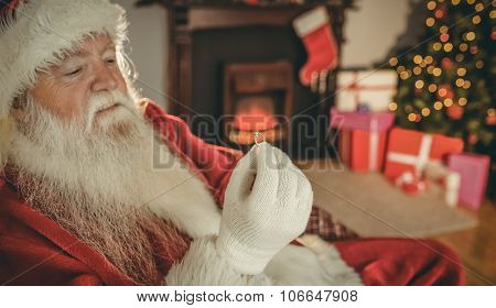 Santa claus holding engagement ring at home in the living room