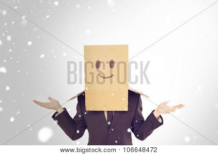 Businessman shrugging with box on head against snow