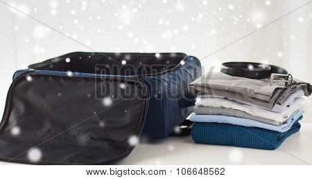 business trip, luggage and clothing concept - close up of travel bag, shirts, trousers and belt over snow effect over snow effect