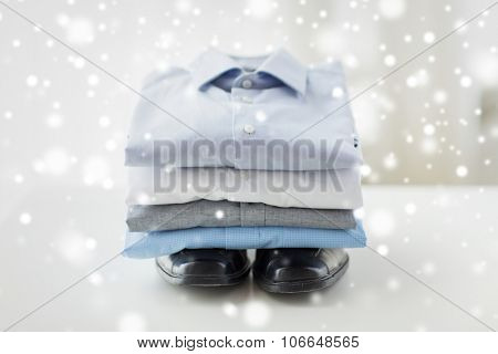 business, style, clothes, housekeeping and objects concept - close up of ironed and folded shirts and formal shoes on table at home over snow effect