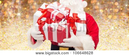 christmas, holidays and people concept - close up of santa claus with gift boxes over lights or golden glitter background
