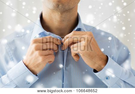 people, business, fashion and clothing concept - close up of man dressing up and fastening buttons on shirt at home over snow effect