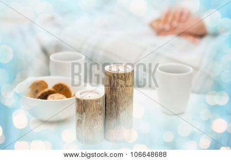 christmas, winter, holidays and concept - close up of candles, cookies and tea cups on table over family couple and blue lights background