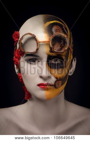 Bald girl with a art make up and steampunk glasses