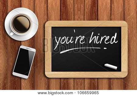 Coffee, Phone  And Chalkboard With Word You're Hired