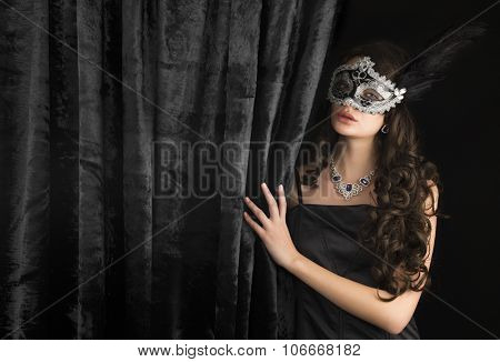 Beautiful woman  in a carnival mask behind the velvet curtain on dark background. Space for text.