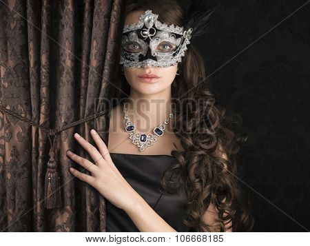 Beautiful woman  in a carnival mask behind the satin embroidered curtain with lace pattern on dark background.
