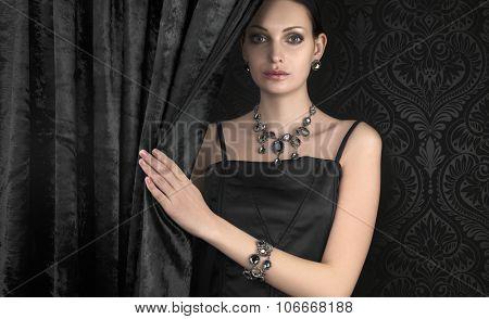 Beautiful woman behind black velvet curtain